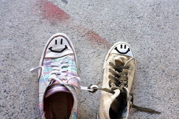 Colourful sneakers with smile face on cement floor