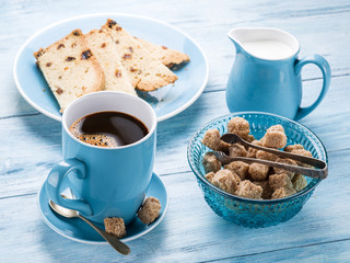 Cup of coffee, milk jug, cane sugar cubes and fruit-cake.