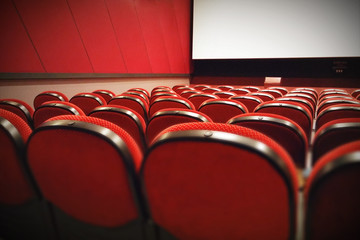 Empty movie theater with red seats, diagonal perspective.