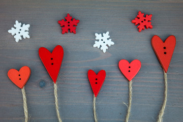 Post card for the Valentine. Button love. Wooden buttons. Button love trees under snowflake on grey wooden background.