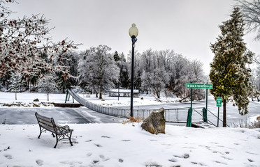 Winter Wonderland. Pastoral winter scene with a footbridge crossing a frozen river. Swinging Bridge Park. Croswell, Michigan.