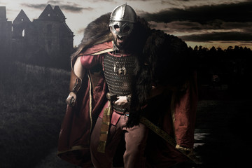 Shouting viking with sword and helmet before castle and sunset g