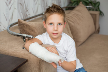 little boy with a broken arm. child in a cast. funny kid after accident.