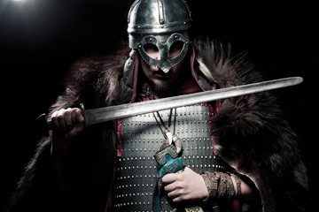 Viking warrior, male dressed in Barbarian style with sword, bear