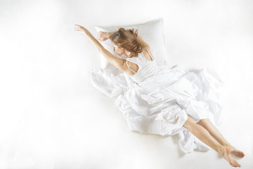 Expressive woman sleeping. Full length high angle view of a young woman sleeping on white background. Expressive woman in action, dreaming concept.
