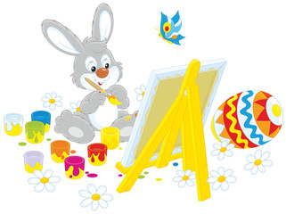 Happy little rabbit drawing a colorfully painted Easter egg on his canvas