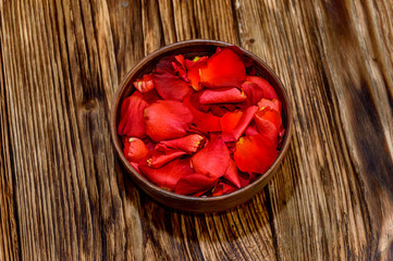 Rose petals in a bowl on a wooden background