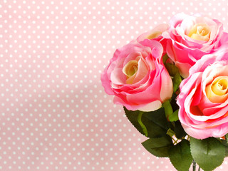 artificial rose flower close up on pink polka dot with space copy background