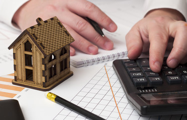 house and the man's hand considers on the calculator