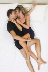 Smiling couple embraced on the bed