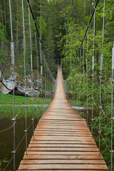 Spoed Foto op Canvas Brug Wooden suspension bridge over the river in the forest