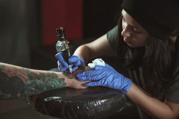 Beautiful brunette girl makes tattoo. Tattooist makes a tattoo. Closeup