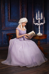 Woman in historic baroque style dress and white wig with a book