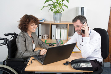 Casual businesswoman in wheelchair working at her desk with man colleague in the office