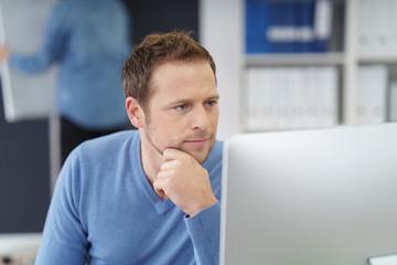 mann im büro schaut konzentriert auf pc