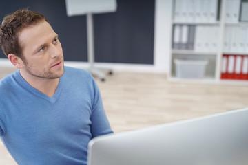 mann im büro schaut fragend zu einem kollegen