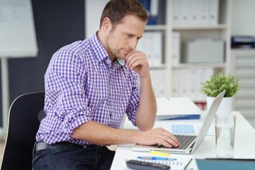 mann sitzt im büro am schreibtisch und schaut auf sein notebook
