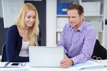 team im büro schaut gemeinsam auf laptop