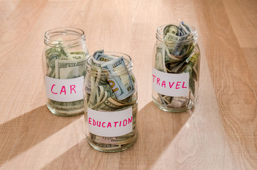 Dollar in glass jar with house, car, education, wedding, travel label, financial concept