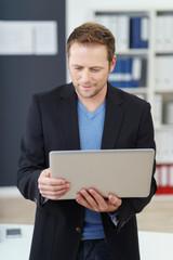 geschäftsmann steht mit laptop im büro