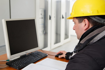 Technician working on the computer  in the power plant control c