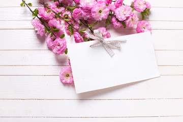 Bright pink   flowers  and empty tag on white  painted wooden pl