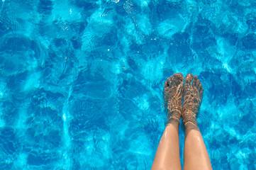 Female legs in the pool water in summer