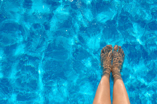 Female legs in the pool water in summer