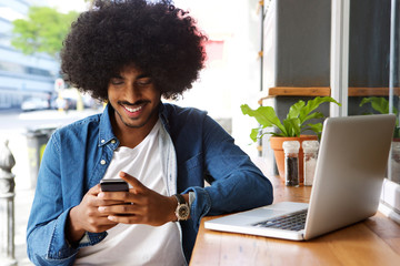 Smiling guy using mobile phone and laptop