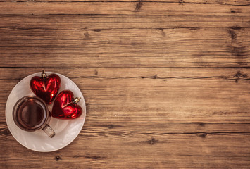 Cup tea and two hearts on wooden background