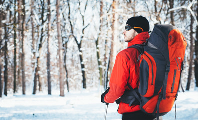 Man hiking at winter mountain/Man hiker trekking in snow forest at winter mountain. Healthy lifestyle winter adventure