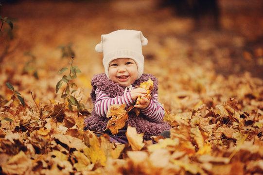 Девочка в шапочке держит листья и улыбается