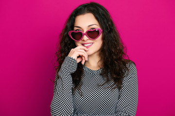 beautiful girl glamour portrait on pink in heart shape sunglasses, long curly hair