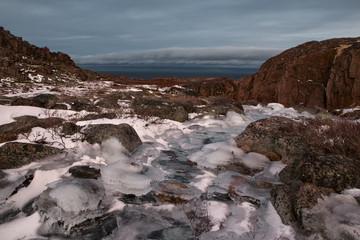 The frozen creek in the rocks on the background of the sea. Murmansk region. Kola Peninsula. Russia.