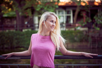 Beautiful young blonde woman on a walk arownd the city near to the castle in summer sunny day