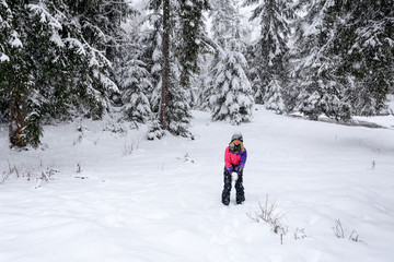Girl play snowballs in winter snow-covered forest