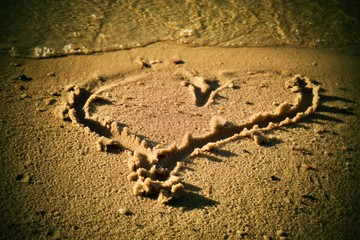 Lovely small heart sketched in salt  sand at beach. Evening warm colors of sunset.