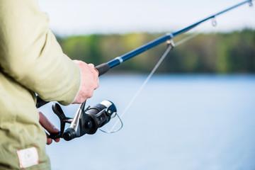 Man fishing with angle at lake