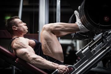 Mann im Fitness Studio an Beinpresse beim Training