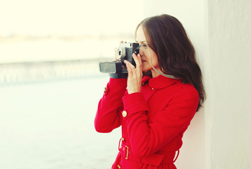 Beautiful young woman with retro vintage camera in winter day, p