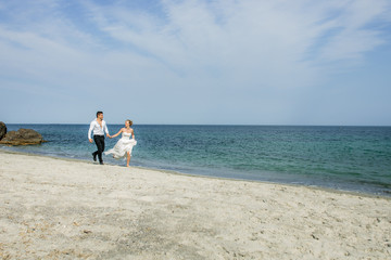 a young couple running at the beach, wedding at the sea, beautiful white wedding dress