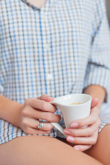 Woman in shirt is sitting on bed with a cup with hot coffee. Bright engagement and wedding rings on her finger.