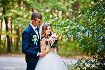 Young lovely wedding couple at the wood