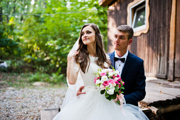 Wedding couple sitting near old wooden house