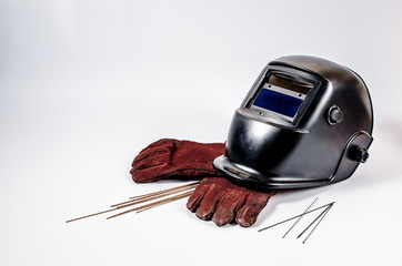 welding mask with red gloves and tungsten rods