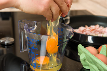 Cracking eggs for breakfast cooking in a modern kitchen