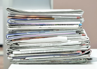 Pile of newspapers at workplace