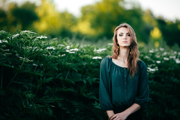 Beautiful young woman posing in a flowering spring park