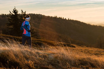 active woman jogging in the mountains in the cold spring morning