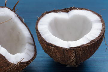 Chopped coconut: coconut halves in the shape of a heart on a blu